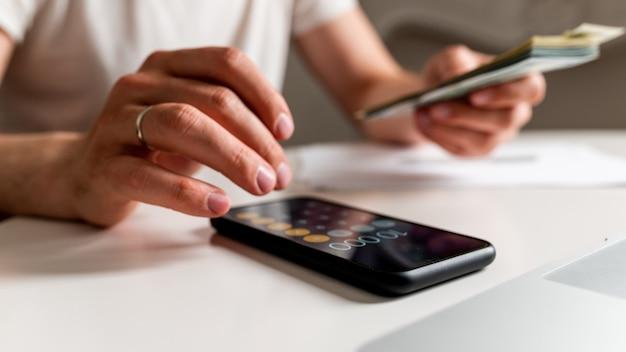 Contabilità tasse e finanze concetto uomo con documenti e calcolatrice che conta soldi a casa il conc...