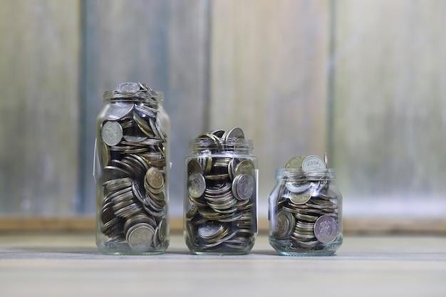 Monete accumulate impilate in barattoli di vetro sul pavimento