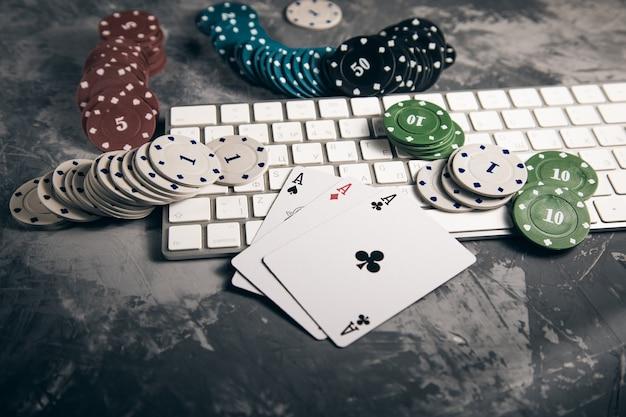 Assi con fiches da poker e tastiera su sfondo grigio
