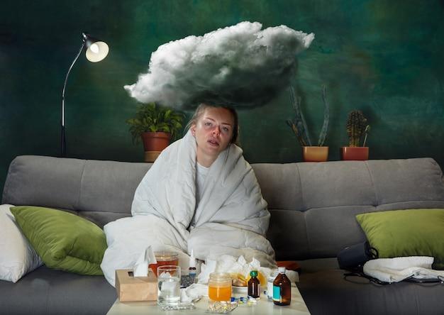 Dolore e febbre. ragazza malata con febbre e raffreddore che si sente male, blu, che tira su con il naso. sembra sofferente e debole, coprendosi con un involucro. freddo, virus, grippe stagionale. donna seduta sul divano di casa.