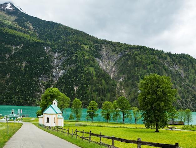 Achensee (lago di achen) paesaggio estivo e chiesa sul prato fiorito (austria).