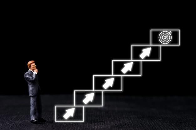 Realizzazione del concetto di obiettivo aziendale, miniatura dell'uomo d'affari in piedi accanto alla scala virtuale