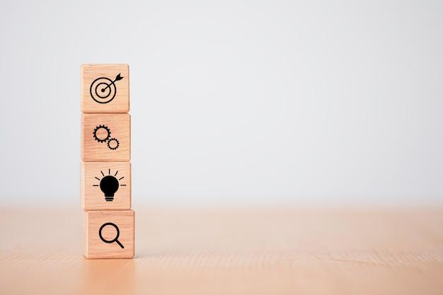 Realizzazione del concetto di obiettivo aziendale, impilamento di blocchi di cubi di legno che stampano l'obiettivo dello schermo, ingranaggi meccanici, lampadina.