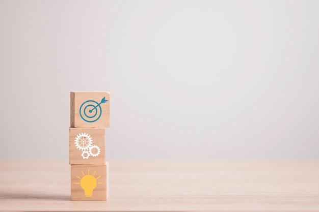 Realizzazione del concetto di obiettivo aziendale, blocco di cubi di legno impilabile che stampa l'obiettivo dello schermo, ingranaggio meccanico, lampadina.