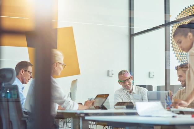 Raggiungere i migliori risultati insieme agli uomini d'affari che hanno una riunione nel moderno ufficio di lavoro