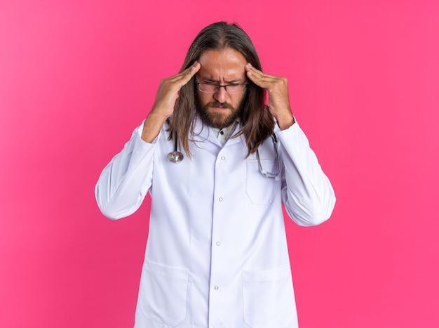 Medico maschio adulto dolorante che indossa tunica medica e stetoscopio con occhiali che tiene le mani sulla testa con gli occhi chiusi isolati sulla parete rosa