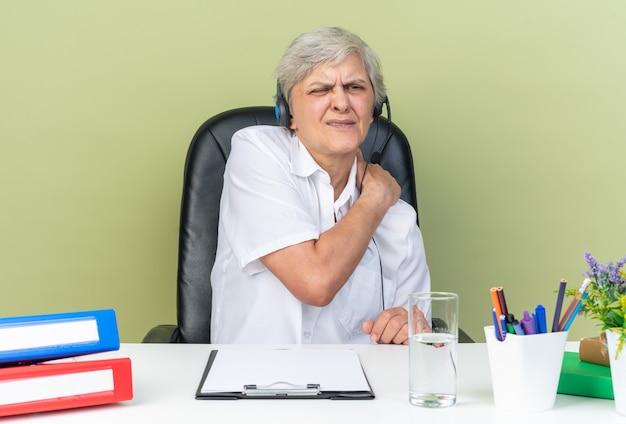 Operatore di call center femminile caucasico dolorante sulle cuffie seduto alla scrivania con strumenti da ufficio che mettono la mano sulla spalla isolata sul muro verde