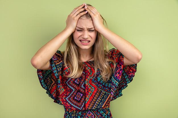 Giovane donna slava bionda dolorante che si mette le mani sulla testa