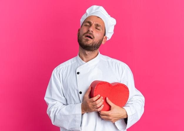 Giovane cuoco maschio caucasico dolorante in uniforme da chef e berretto che tiene a forma di cuore con gli occhi chiusi isolati su parete rosa