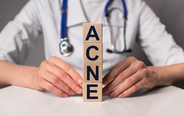 Parola di acne, iscrizione su carta nelle mani del medico, problema di dermatologia medica con la pelle.