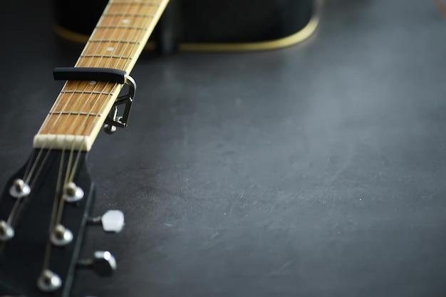 Una chitarra acustica per un artista che suona uno strumento musicale a corde sul palco. chitarra nera con capotasto. sottofondo musicale.