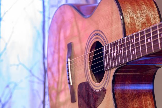 Chitarra acustica su un bellissimo sfondo colorato. concetto di strumenti a corda.