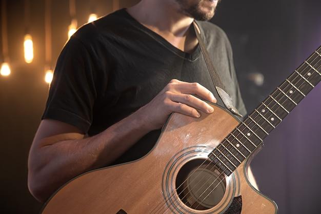 Chitarra acustica nelle mani di un chitarrista in un concerto su uno sfondo sfocato nero.