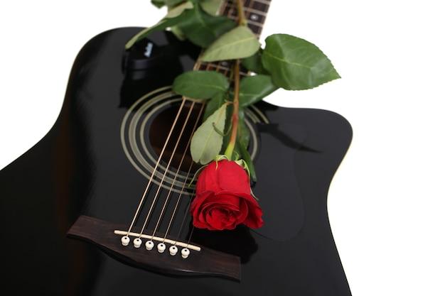 Chitarra acustica e fiore della rosa rossa, isolato su bianco