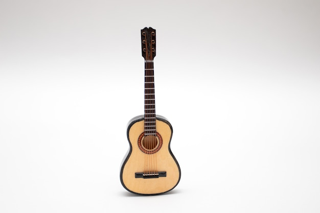 Chitarra acustica piccolo giocattolo in miniatura su sfondo bianco