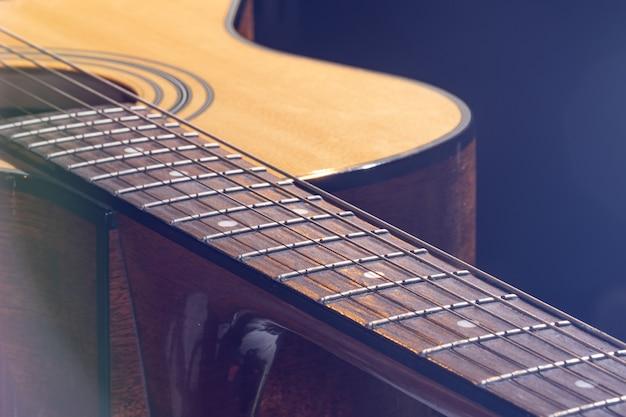 Chitarra acustica con un bellissimo legno su sfondo nero alla luce di un riflettore.