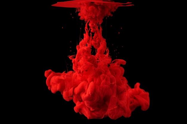 L'inchiostro acrilico in acqua forma un modello di fumo astratto isolato sulla superficie nera