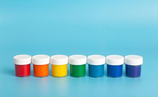 Vernice acrilica nei colori dell'arcobaleno su sfondo azzurro. vernice per la pittura, concetto di colori dell'arcobaleno.