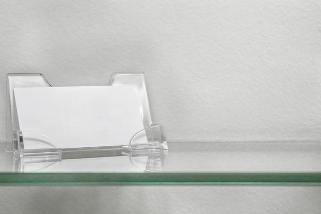 Supporto in carta acrilica per scheda vuota, supporto del biglietto da visita sulla mensola di vetro isolato