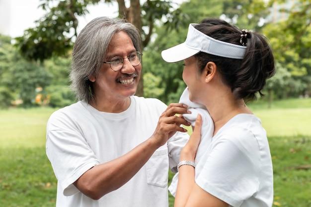L'anziano asiatico attivo delle coppie in abiti sportivi sta pulendo il sudore dopo l'esercizio nel parco.