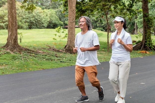 Anziano asiatico attivo delle coppie in abiti sportivi che pareggiano al parco.