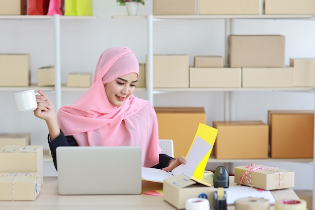 Donna musulmana asiatica attiva che indossa un abito seduto e tiene in mano una cartella con il computer e la consegna della scatola del pacchetto online. startup piccola impresa concetto freelance.
