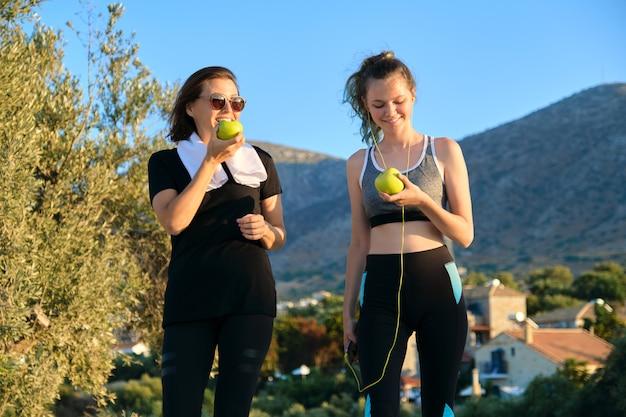 Attivo stile di vita familiare atletico sano, madre felice sorridente e figlia adolescente che mangiano mele, riposando dopo esercizi di jogging. bellissimo sfondo della natura di montagna al tramonto