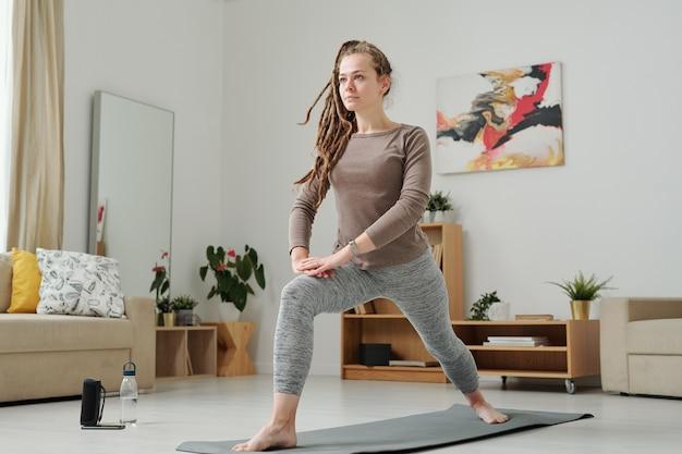 Donna attiva a piedi nudi in leggins e pullover che allunga le gambe mentre si trova sul tappeto durante l'allenamento a casa