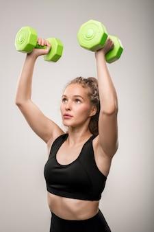 Ragazza bionda attiva in abiti sportivi neri che tiene manubri verdi in mano sulla testa durante l'esercizio fisico su grigio
