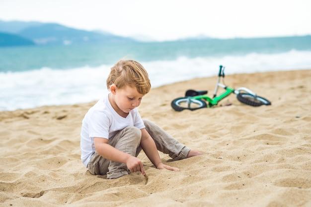 Ragazzo biondo attivo del bambino che guida la bicicletta nel parco vicino al mare
