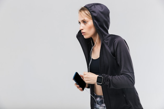 Donna bionda attiva vestita di abbigliamento sportivo che ascolta la musica con le cuffie mentre è in esecuzione isolata su un muro bianco