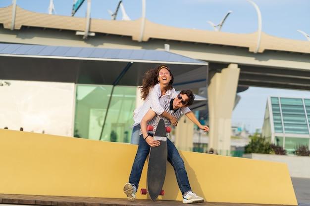 La giovane coppia attiva e spensierata si diverte insieme: donna alla moda che trasporta sulle spalle il fidanzato. gli amanti della ragazza e del ragazzo simpatici skateboarder ridono rilassarsi sullo sfondo del parco skate dello spazio urbano moderno. amore e libertà