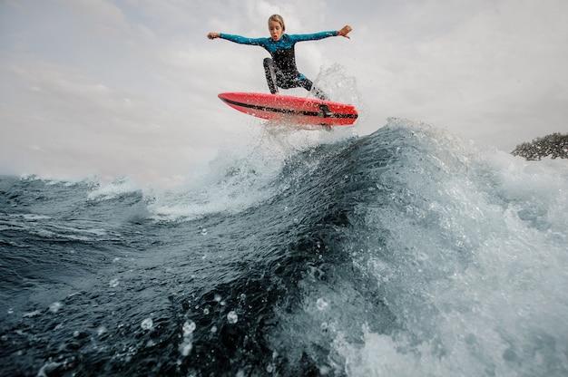 Il ragazzo attivo del bambino si è vestito in surf del costume da bagno che salta su sul bordo arancio