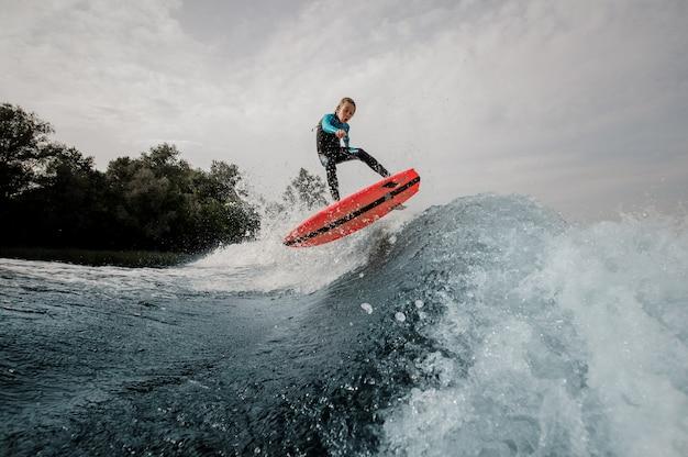 Il ragazzo attivo del bambino si è vestito in costume da bagno che pratica il surfing sul bordo arancio