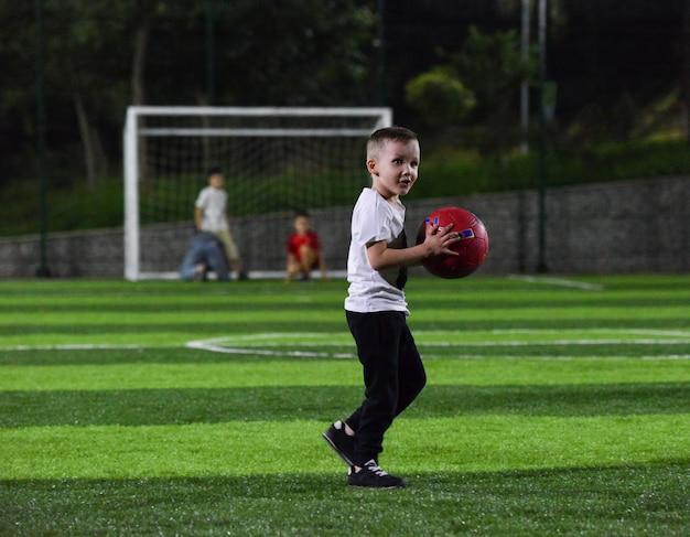 Il bambino attivo sta giocando con una palla rossa sul campo di calcio, di notte