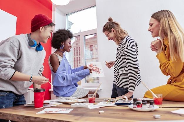 Discussione attiva. quattro begli studenti intelligenti del dipartimento di moda che discutono attivamente