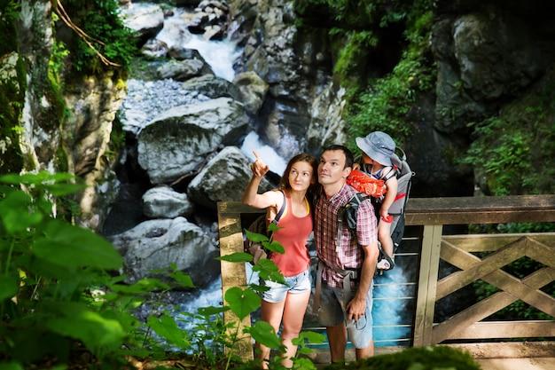 Escursioni attive in famiglia con bambino di 15 anni in marsupio sullo sfondo di un fiume di montagna
