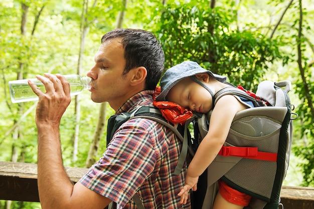 Escursioni attive in famiglia con bambino di 15 anni in marsupio sullo sfondo di una natura slovenia