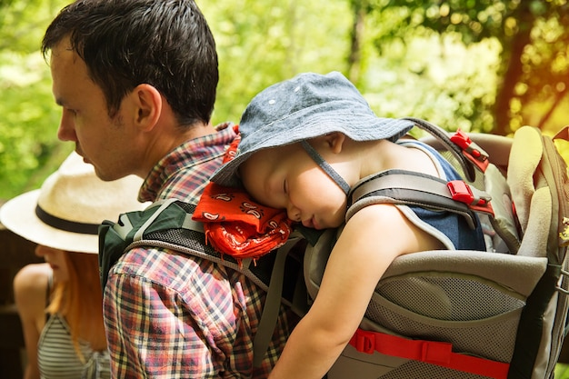 Escursioni attive in famiglia con bambino di 15 anni in marsupio sullo sfondo di una natura