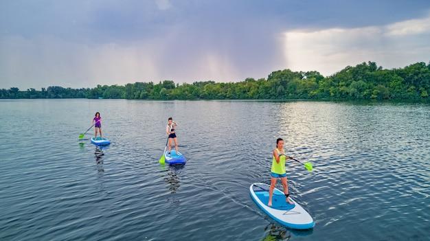 Famiglia attiva su sup, in piedi paddleboard, in acqua di fiume, sport estivi per famiglie, vista aerea dall'alto dall'alto