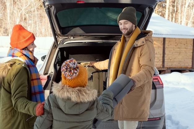 Famiglia attiva di tre persone in abiti invernali caldi che mettono il loro passeggino nel bagagliaio mentre sono in piedi sul retro dell'auto, giovane che prende un tappetino arrotolato