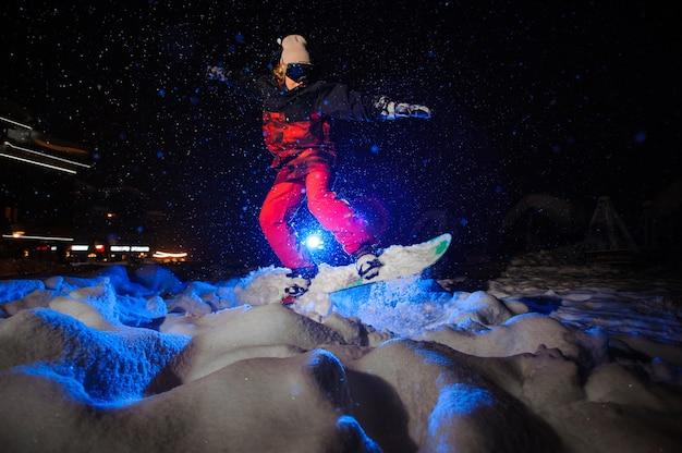Snowboarder femminile attivo vestito con un abbigliamento sportivo rosso che salta sul pendio della montagna nella notte sotto la luce blu