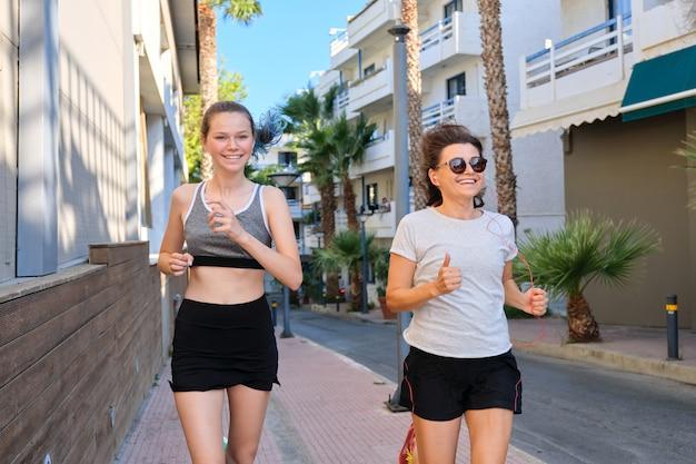 Famiglia sportiva amichevole attiva, adolescente madre e figlia che corrono insieme. priorità bassa della via della città tropicale, belle donne da jogging felici