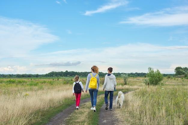 Stile di vita sano attivo, bambini all'aperto con il cane, ragazzo di famiglia e ragazze che camminano lungo la strada di campagna, vista posteriore