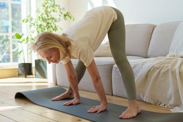 Donna anziana attiva e sana in piedi nella posa yoga del cane rivolta verso il basso mentre pratica lo yoga a casa