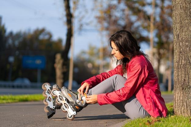 Tempo libero attivo. una ragazza sportiva è rollerblade in un parco in autunno.