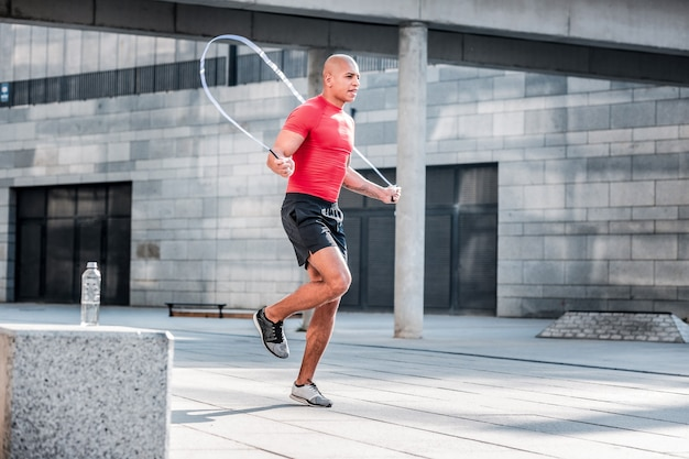 Stile di vita attivo. uomo atletico che lavora duro che salta su una corda per saltare mentre ha un allenamento