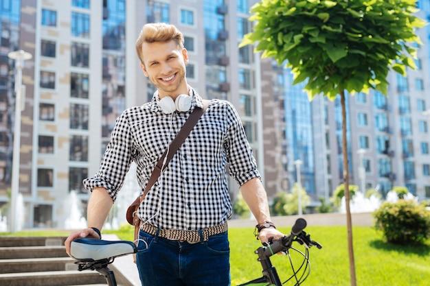 Stile di vita attivo. piacevole uomo simpatico che tiene la sua bici mentre è nel parco