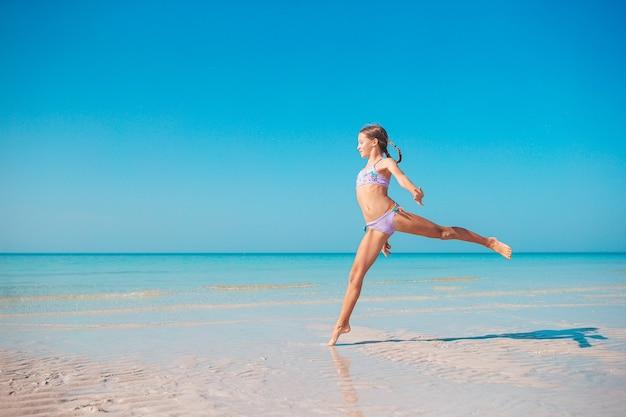 Bambina attiva sulla spiaggia divertendosi molto in acque poco profonde