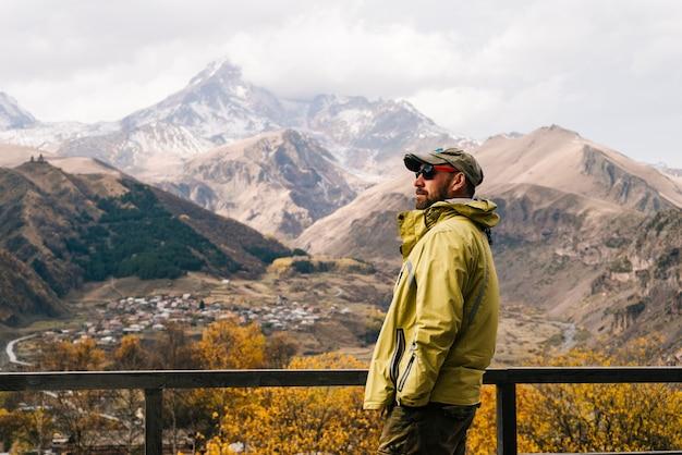 Il viaggiatore maschio attivo in occhiali da sole gode della natura e delle avventure di montagna